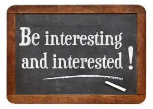 be interesting and interested -  social media reminder and concept - white chalk text  on a vintage slate blackboard